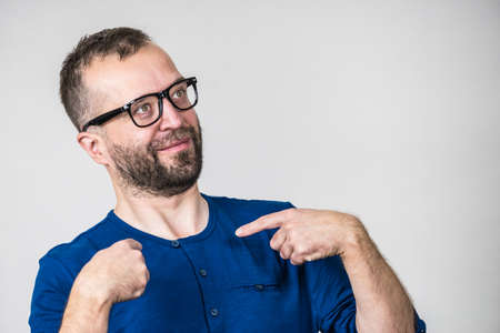 Adult man wearing eyeglasses being shocked, having surprised face expression. Studio shot Banco de Imagens