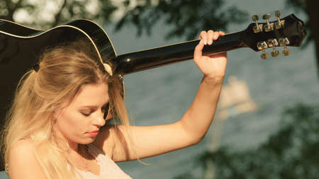 Hippie looking young adult woman wearing gypsy outfit having acoustic guitar. Female playing music in park. Imagens