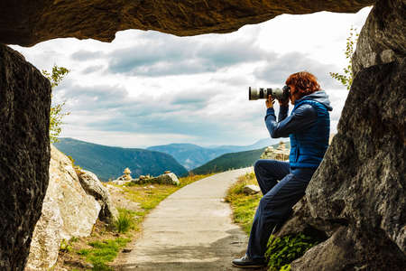 Woman with camera on Vedahaugane viewpoint at entrance to underground cave. National Tourist Route Aurlandsfjellet. 版權商用圖片