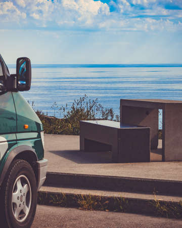 Camper car on rest stop area, viewpoint with stone seating bench on sea ocean shore. Attractions along Lofoten islands in Norway. Stok Fotoğraf