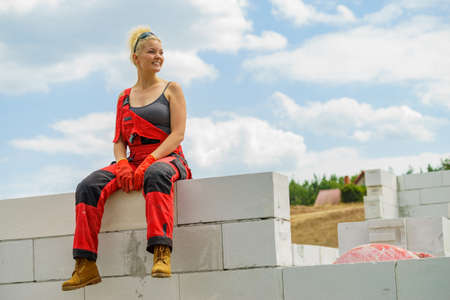 Woman wearing workwear on construction site. Female takes break from work, sitting on wall. Partially built new house early stage. Industry. Foto de archivo - 124964972