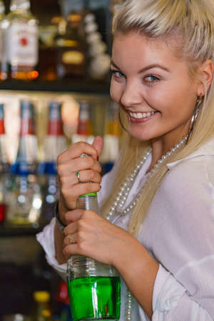 Woman working at the bar counter, holding alcohol bottle