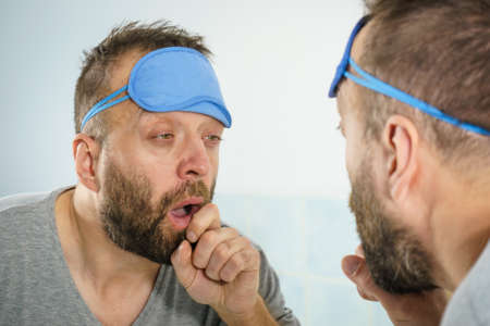 Funy adult man wearing eyemask on forhead having troubles with waking up. Standing in front of mirror looking at his face, being tired and sleepy. Imagens - 124964978