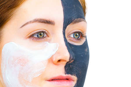 Woman with clay carbo black mask on half face applying white mud to clean skin. Girl taking care of oily complexion. Beauty procedures. Skincare. Reklamní fotografie
