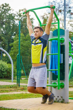 Young handsome man working out in outdoor gym. Sporty guy flexing his muscles doing pull ups on machine. Staying fit and healthy. Stock Photo