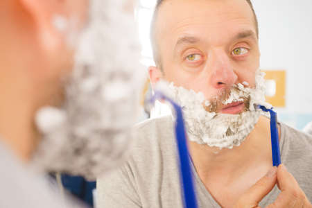 Man with lots of shaving foam on his face standing in bathroom, looking at mirror, shaving his face beard. Skincare Reklamní fotografie