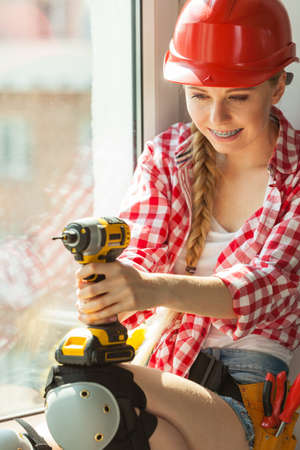 Young determinated woman using drill doing home renovation. Female construction worker having driller tool Banco de Imagens