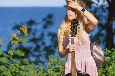Hippie looking young adult woman wearing gypsy outfit having acoustic guitar. Female playing music in park. Stock Photo
