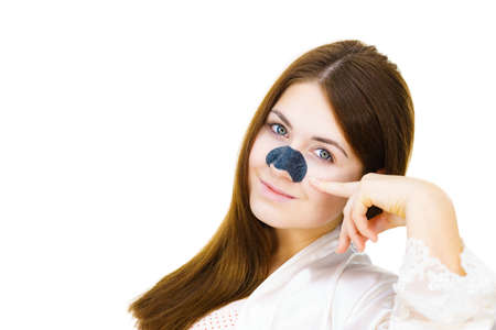 Woman appying clear-up strips on nose, using pore cleansing textile mask, against white. Girl taking care of skin complexion. Beauty treatment. Skincare.