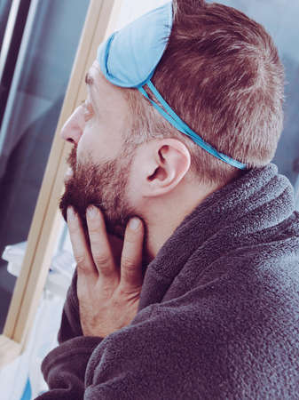 Funny adult man wearing eyemask on forhead having troubles with waking up. Standing in front of mirror investigating imperfections on his face.