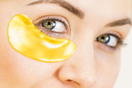 Woman applying golden collagen patches under eyes. Mask removing wrinkles and dark circles. Female taking care of delicate skin around eye. Beauty treatment.