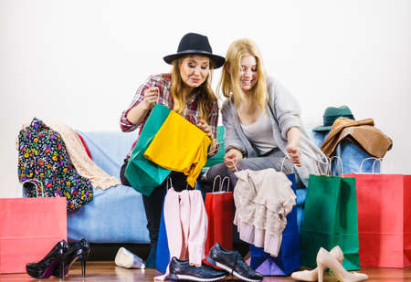 Two happy joyful women having fun after shopping, picking outfit in closet. Female friends fooling around.
