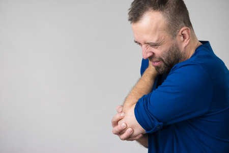 Man feeling pain in elbow having arm joints injury. Health rheumatism problems conept. Banque d'images