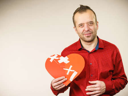 Healed love. Valentines Day concept. Adult smiling man holding big red heart with plaster. Male healing relationship. Banco de Imagens