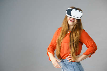 Smiling positive woman wearing virtual reality goggles headset, vr box. Connection, technology, new generation and progress concept. Studio shot on gray