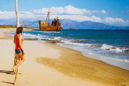 Travel freedom. Mature tourist woman on beach enjoying summer vacation. An old abandoned shipwreck, wrecked boat in the background Imagens