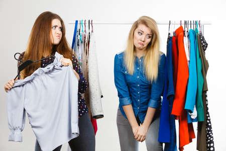 Twee grappige vrouwen hebben ruzie tijdens het winkelen over kledingstuk. Verkoopgekte, blond meisje dat verdrietig is