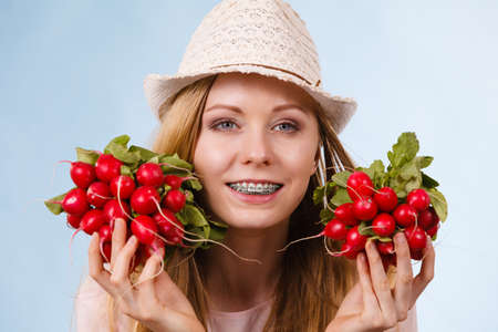 Happy teenage young woman ready for summer wearing pink outfit and sun hat giving showing delicious radish Imagens