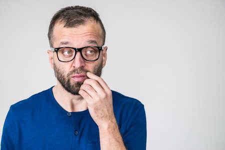 Un homme intelligent adulte portant des lunettes et une chemise bleue ayant une expression de visage concentrée et réfléchie. Homme se concentrant sur son travail, contemplant l'idée.