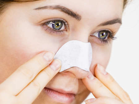 Woman appying clear-up strips on nose, using pore cleansing textile mask Girl taking care of skin complexion. Beauty treatment. Skincare.