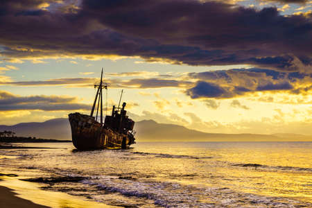 An old abandoned shipwreck, wrecked boat sunken ship stand on beach coast. Scenic sunset sky Foto de archivo