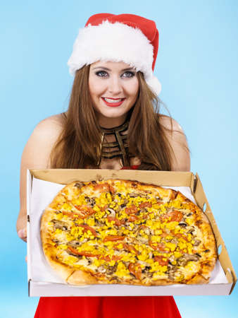 People, italian cuisine concept. Young woman in christmas santa hat holding hot fresh big pizza in box, on blue. Delicious fast food meal. Delivery service. Stock Photo