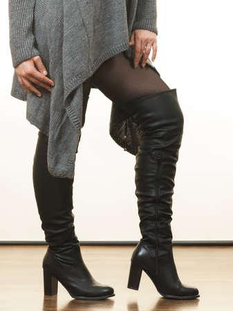 Nicht erkennbare Frau, die graue lange Top-Pullover-Tunika, schwarze Strumpfhose trägt. Stilvolles, herbstliches Outfit.