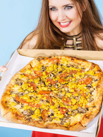 People, italian cuisine concept. Young woman holding hot fresh big pizza in box, on blue. Delicious fast food meal. Delivery service.