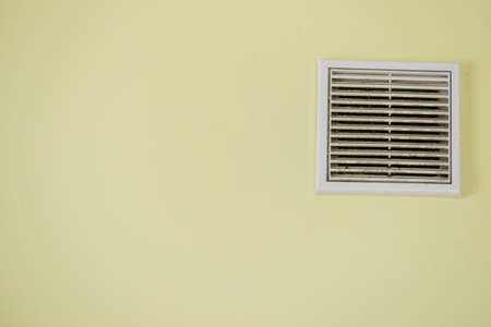 Home details concept. View of yellow wall with vent system. Interior cooling device. Stock Photo