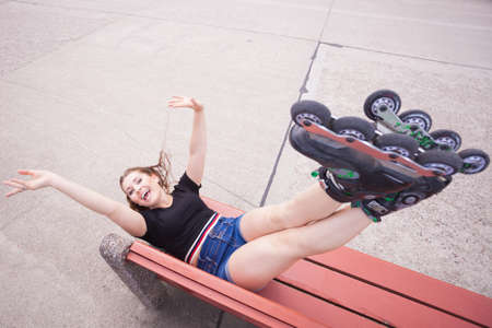 Happy joyful young woman wearing roller skates lying on bench with raised legs. Bizarre high angle