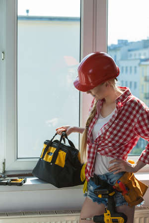Pretty young woman construction worker with helmet about to fix window picking best tools. Working at flat remodeling. Building, repair and renovation. Stockfoto