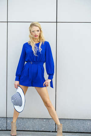 Fashionable woman wearing blue jumpsuit shorts perfect for summer holding elegant stylish sun hat. Fashion model outdoor photo shoot Imagens