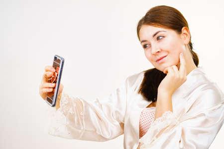 Młoda kobieta, brązowe włosy bez makijażu, ubrana w bieliznę, robiąca zdjęcie selfie, używająca telefonu z dekoracją na plecach