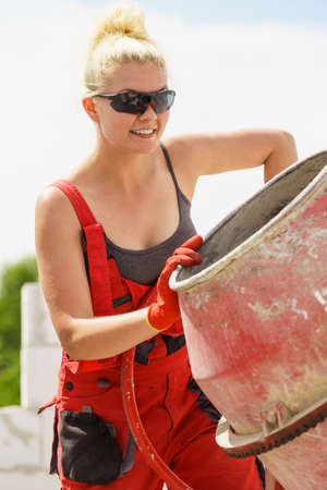 Strong woman worker working with red concrete cement mixer machine on house construction site. Industrial work equipment concept.