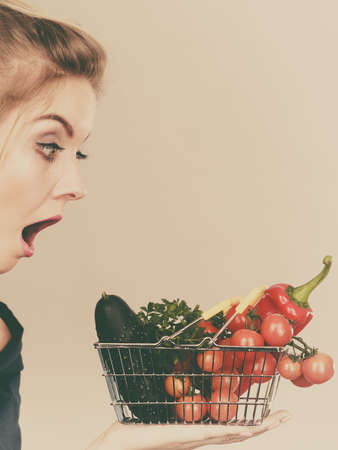 Adult woman do not like to eat raw food, questioning healthy lifestyle recommendations, origin vegetagles. Female holding small shopping basket with products, displeased shocked face expression Stock Photo