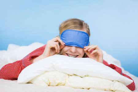 Sleepy young woman wearing sleeping eye band lying in bed before going to sleep. Reklamní fotografie