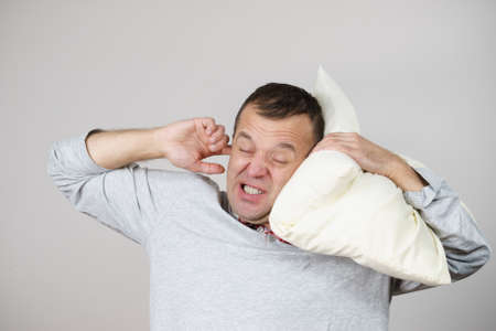 Sleepy tired angry guy holding pillow in one and closing his ear with another hand protecting from noise, on grey. Health care, sleep disorder concept