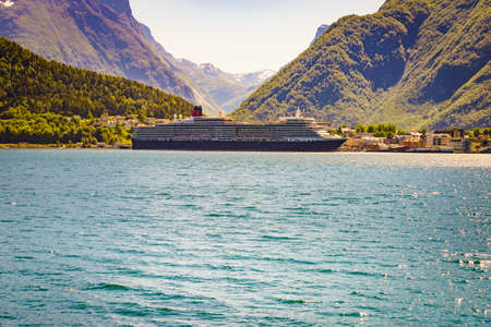 ANDALSNES, NORWAY - JULY 10, 2018: The luxury cruise ship Queen Elizabeth operated by the Cunard Line docked in port Andalsnes in Rauma Municipality.