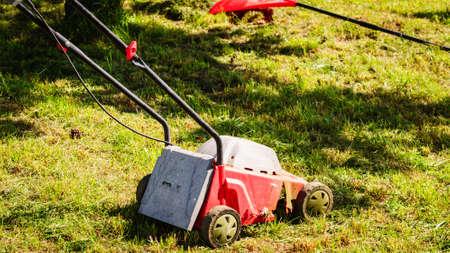 Tuinieren, tuin service. Oude grasmaaimachine die groen gras in binnenplaats snijdt. Maaiend gebied met grasmaaier in zonnige dag.