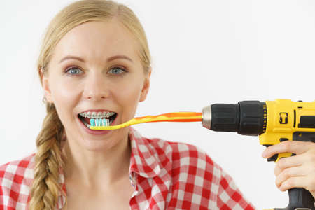 Funny teenage woman wearing braces holding drill about to brush her teeth with toothbrush