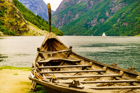 Old wooden viking boat on seashore in norwegian nature and ferryboat on fjord. Mountains and Sognefjord. Tourism and traveling concept