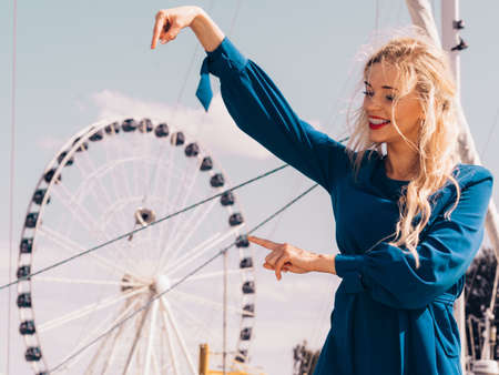 Fashionable woman wearing blue jumpsuit shorts perfect for summer. Fashion model outdoor photo shoot posing against ferris wheel Stock Photo