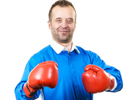 Mid adult man in blue sweater with white shirt collar wearing red boxing gloves being ready to fight. Studio shot on isolated background.