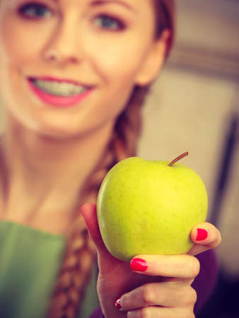 Woman young female long haired holding big green yellow apple fruit. Healthy eating, vegetarian food, dieting and people concept.