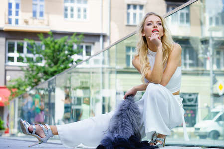 Glamurous female fashion model presenting casual elegant outfit. Woman wearing crop top and holding fur scarf. Summer urban outfit, outdoor photo session.
