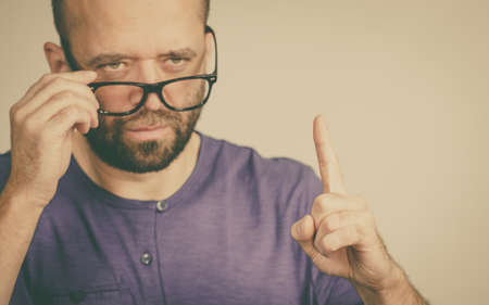 Adult rude man wearing eyeglasses being overbearing, commanding pointing with his finger