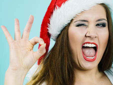 Happy joyful girl wearing santa claus hat giving thumb up ok sign, on blue. Christmes time.