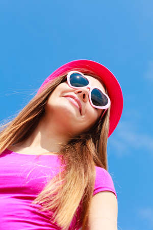 Accessories, female summer fashion, sun protection concept. Smiling beautiful woman wearing heart shaped sunglasses and red hat looking at sky, outdoor shot on sunny day.