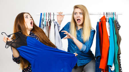 Two funny women arguing with each other during shopping about piece of clothing. Sales madness Imagens