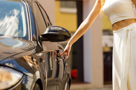 Glamurous female fashion model, elegant woman opening car holding handle to her exclusive auto